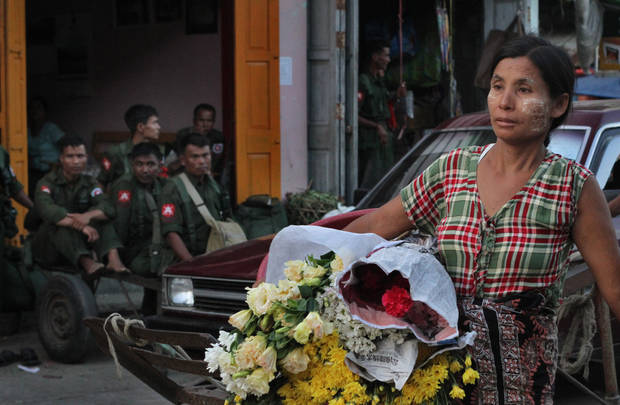 In this photo taken Nov. 9, 2012, a woman carries flowers at local bazaar as Myanmar soldiers rest in the back ground in Sittwe township, Rakhine state, western Myanmar. Stranded beside their decrepit flotilla of wooden boats, on a muddy beach far from home, the Muslim refugees tell story after terrifying story of their exodus from a once-peaceful town on Myanmar's western coast. The Oct. 24 exodus was part of a wave of violence that has shaken western Myanmar twice in the last six months.  (AP Photo/Khin Maung Win)