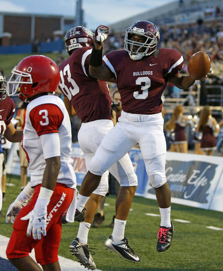 Edmond Memorial's Waylan Anderson, at right, celebrates with Donovan Nunley after a touchdown as Lawton's Kalin Sadler walks past during their high school football game at Wantland Stadium in Edmond, Okla., Friday, Sept. 27, 2013. Photo by Bryan Terry, The Oklahoman