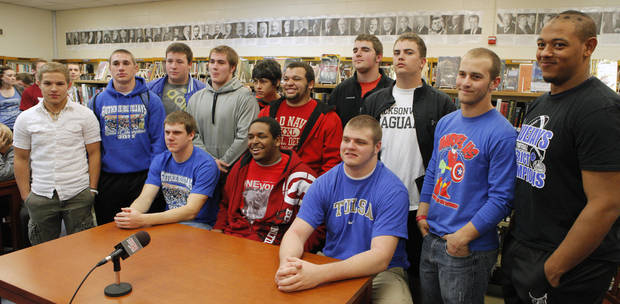 Seated at the table are Clint Simek, signing with UCO, LaMarc Allison, signing with Langston, and Blake Belcher, signing with TU, surrounded by fellow senior athletes during a signing ceremony in the library at Guthrie High School in Guthrie Wednesday, Feb. 1, 2012. Photo by Paul B. Southerland, The Oklahoman