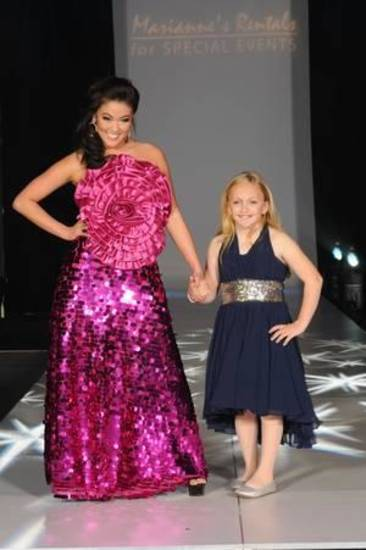 "Miss Oklahoma 2012 Alicia Clifton with a ""Miracle Child"" at last year's Linen Runway Fashion Show."