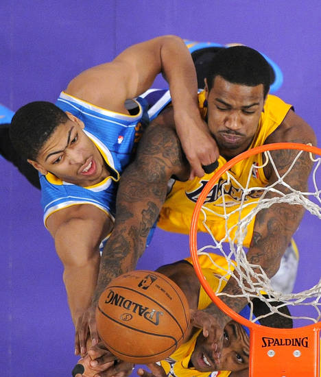 New Orleans Hornets forward Anthony Davis, left, breaches for a rebound with Los Angeles Lakers forward Earl Clark, top right, and center Dwight Howard during the first half of an NBA basketball game, Tuesday, Jan. 29, 2013, in Los Angeles. (AP Photo/Mark J. Terrill)
