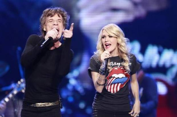 "In this photo taken Saturday, May 25, 2013, Carrie Underwood sings ""Only Rock'n Roll"" with Mick Jagger of the Rolling Stones at the Air Canada Center, in Toronto. (AP)"
