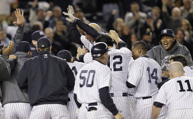 New York Yankees' Raul Ibanez celebrates with teammates as he reaches home plate after hitting the game-winning home run during the 12th inning of Game 3 of the American League division baseball series against the Baltimore Orioles on Wednesday, Oct. 10, 2012, in New York. The Yankees 3-2. (AP Photo/Kathy Willens)
