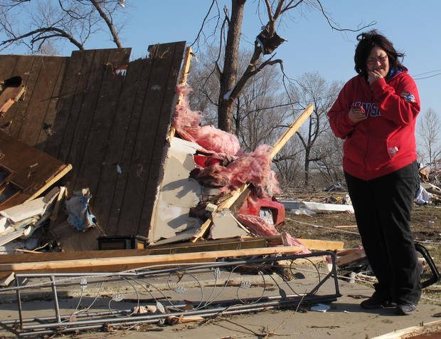 Tammy Woodyard, of Harveyville, surveys the wreckage of her father's home the morning after a tornado hit the town, Wednesday, Feb. 29, 2012, in Harveyville, Kan. Her father was unhurt. (AP Photo/John Hanna) ORG XMIT: RPJH103