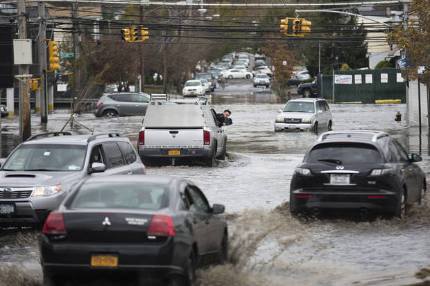 A passenger inspects the water level around his vehicle as multiple cars drive through  a flooded street, Wednesday, Oct. 31, 2012, in the Staten Island borough of New York. Sandy, the storm that made landfall Monday, caused multiple fatalities, halted mass transit and cut power to more than 6 million homes and businesses. (AP Photo/ John Minchillo) ORG XMIT: NYJM112