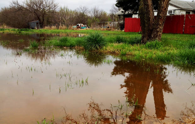 Water ponds in a field next to a home in the Crutcho Creek area of Midwest City Thursday morning near NE 19 and Godlin. Photo by Jim Beckel
