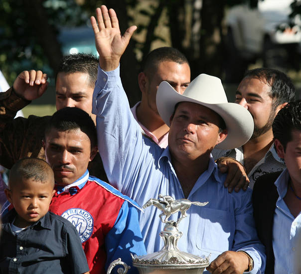 Jose Trevino Morales, center, acknowledges the crowd as he stands with the trophy after Mr. Piloto won the All American Futurity horse race in September 2010 at Ruidoso Downs, N.M. AP photo