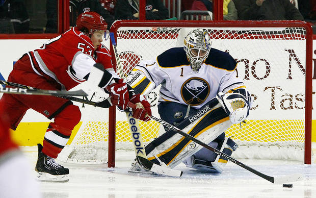 Carolina Hurricanes' Jeff Skinner (53) works the puck in front of Buffalo Sabres' Jhonas Enroth (1) during the second period of an NHL hockey game in Raleigh, N.C., Thursday, Jan. 24, 2013. (AP Photo/Karl B DeBlaker)