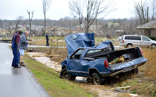 People look at a truck that was blown off the road by debris from a reported tornado that passed through the Harvest, Ala., area Friday, March 2, 2012. (AP Photo/The Huntsville Times, Bob Gathany) ORG XMIT: ALHUT107