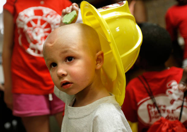 Cancer patient Jaxon Dugger, 3, lifts his fireman's hat at the Warr Acres fire station, Wednesday, July 24, 2013. Photo by Bryan Terry, The Oklahoman