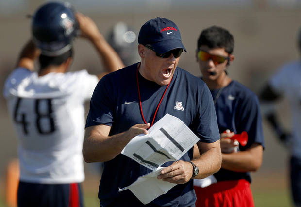 FILE - This Aug. 9, 2012 file photo shows University of Arizona football coach Rich Rodriguez calling out to his players as they run drills during team practice in Sierra Vista, Ariz.  (AP Photo/Arizona Daily Star, Kelly Presnell)