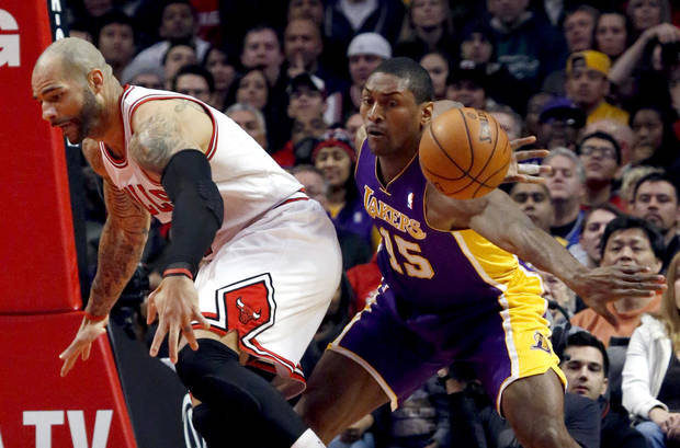 Los Angeles Lakers forward Metta World Peace (15) knocks the ball away from Chicago Bulls forward Carlos Boozer during the first half of an NBA basketball game, Monday, Jan. 21, 2013, in Chicago. (AP Photo/Charles Rex Arbogast)