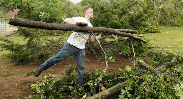 Jayme Shelton clears a tree limb from the home of his in-laws in the Timberlake Estate neighborhood after a tornado moved through Edmond, Okla., Sunday, May 19, 2013. Photo by Nate Billings, The Oklahoman