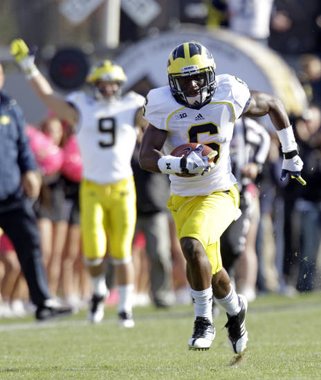 Michigan defensive back Raymon Taylor returns an interception for a 63-yard touchdown against Purdue during the first half of an NCAA college football game in West Lafayette, Ind., Saturday, Oct. 6, 2012. (AP Photo/Michael Conroy)