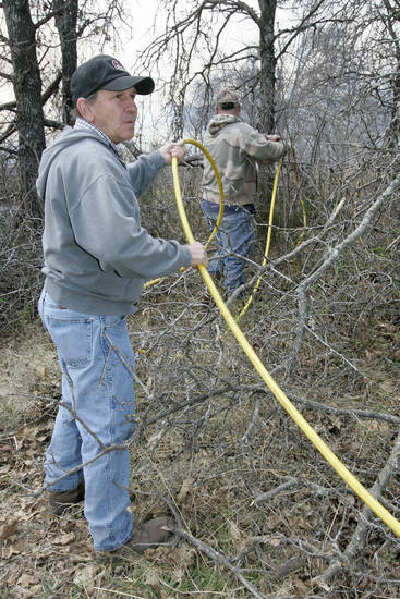 George Jennings works with Steve Hill to make sure firefighters have enough hose to keep fire away from a trailor on neighbors land east of Stanley Draper near Anderson road. Fri. April 10, 2009. Photo by Jaconna Aguirre, The Oklahoman