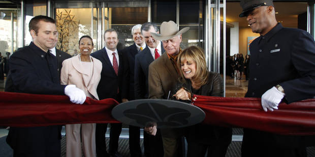 Linda Gray cuts the ribbon as Larry Hagman holds the ribbon at the grand opening of the Omni Dallas Hotel on Friday, November 11, 2011. In the background, Hattie Hill, Chairman of the Dallas Convention & Visitors Bureau, Jack Matthews, Former Dallas Mayor Tom Leppert, and Dallas Mayor Mike Rawlings look on. Hagman, who for more than a decade played villainous patriarch JR Ewing in the TV soap Dallas, has died at the age of 81, his family said Saturday Nov. 24, 2012. (AP Photo/David Woo, The Dallas Morning News)