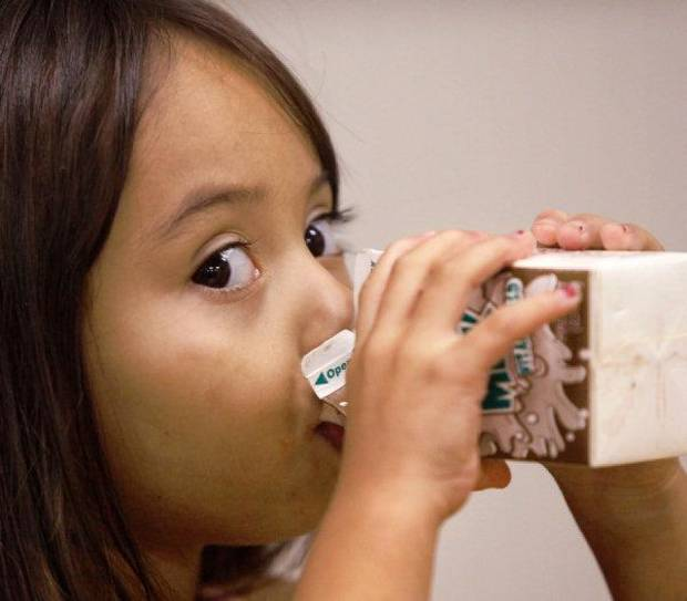 Renee Alvarado, 4, drinks from a milk carton during an afternoon meal. She is  among dozens of children who are receiving healthy snacks and meals through a summer feeding program for children.  Novo Ministries partnered with  the Regional Food Bank Of Oklahoma to feed the children during the summer months while they are out of school. These children are at the Ambassador Courts Community Center.  <strong>JIM BECKEL - THE OKLAHOMAN</strong>
