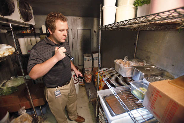 Oklahoma City-County Health Department inspector Jacob Custer inspects the walk-in cooler recently in a restaurant in Midwest City. Photo By David McDaniel, The Oklahoman