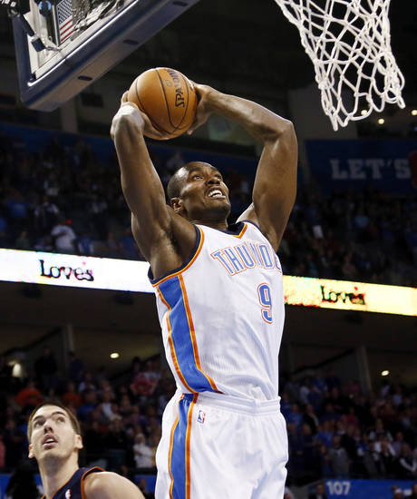 Oklahoma City's Serge Ibaka (9) dunks the ball past Charlotte's Byron Mullens (22) during an NBA basketball game between the Oklahoma City Thunder and Charlotte Bobcats at Chesapeake Energy Arena in Oklahoma City, Monday, Nov. 26, 2012.  Photo by Nate Billings , The Oklahoman