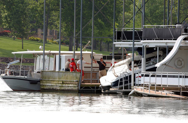 Officals beside the boat that crashed into a houseboat docked leaving 2 dead at Arrowhead Resort on Grand Lake.  Gary Crow/For the Oklahoman