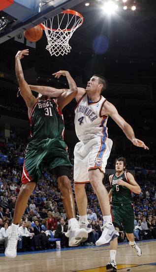 Nick Collison (4) of the Thunder fouls Charlie Villanueva (31) of the Bucks during the NBA basketball game between the Oklahoma City Thunder and the Milwaukee Bucks at the Ford Center in Oklahoma City, Wednesday, Oct. 29, 2008. This was the regular season debut of the Thunder. Milwaukee won, 98-87. BY NATE BILLINGS, THE OKLAHOMAN
