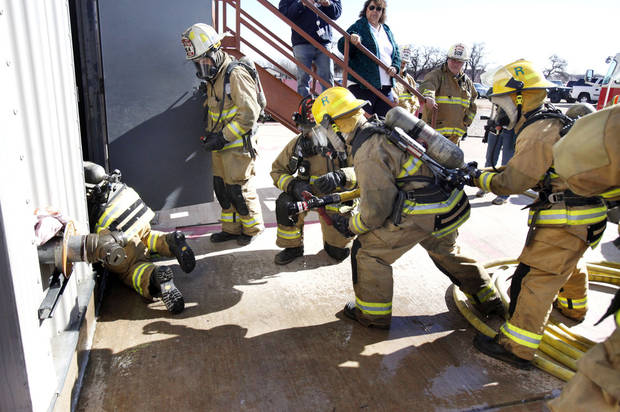 Trainees enter a smoky building during live fire drills for fire department recruit training at the Eastern Oklahoma County Vo-Tech in Choctaw, OK, Monday, Jan. 30, 2012. By Paul Hellstern, The Oklahoman