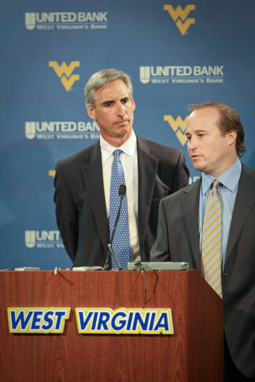 West Virginia Athletic Director Oliver Luck, left, and head football coach Dana Holgorsen, right, wait for the start of a press conference to announce the resignation of Bill Stewart and the appointment of Holgorsen as head coach in Morgantown, W.Va. on Friday, June 10, 2011. (AP Photo/David Smith)
