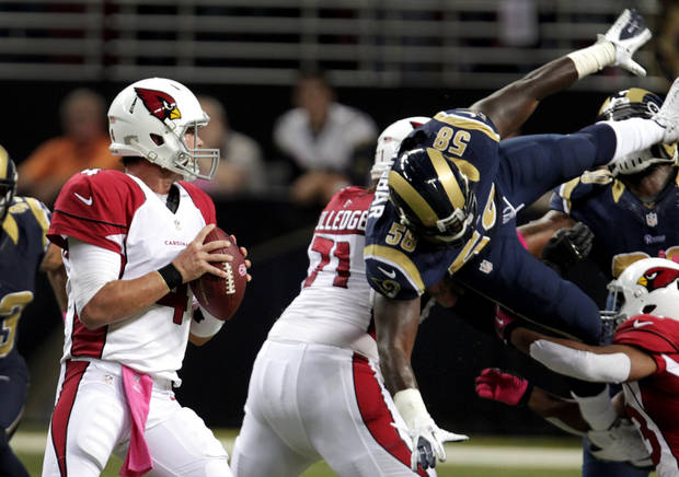 Arizona Cardinals quarterback Kevin Kolb, left, looks to throw as St. Louis Rams outside linebacker Jo-Lonn Dunbar (58) dives through the line during the first quarter of an NFL football game, Thursday, Oct. 4, 2012, in St. Louis. (AP Photo/Tom Gannam)