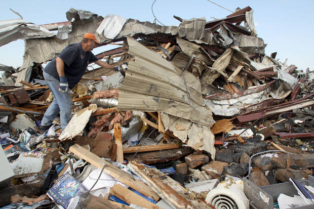 Matt Asbill digs through the wreckage of his  business. AP Photo