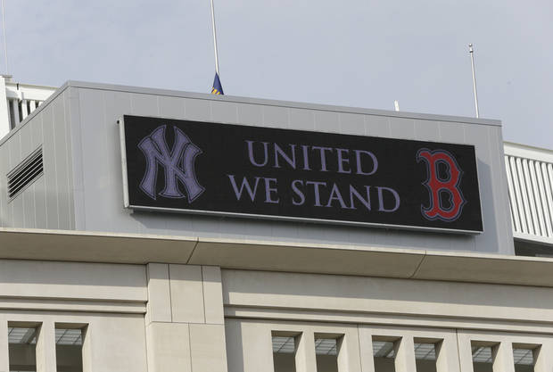 "A sign that reads ""United We Stand"" between logos for the New York Yankees and the Boston Red Sox appears at the top of Yankee Stadium before a baseball game in New York, Tuesday, April 16, 2013. The message was displayed in the wake of the Boston Marathon explosions. (AP Photo/Kathy Willens)"