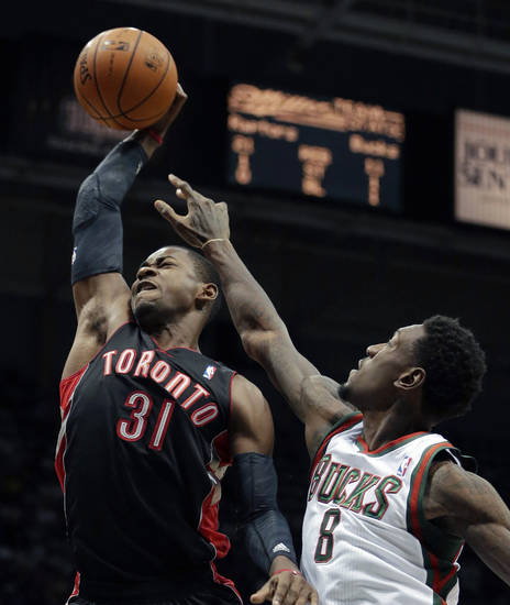 Toronto Raptors' Terrence Ross is fouled as he tries to shoot past Milwaukee Bucks' Larry Sanders during the first half of an NBA basketball game Saturday, Nov. 2, 2013, in Milwaukee. (AP Photo/Morry Gash)