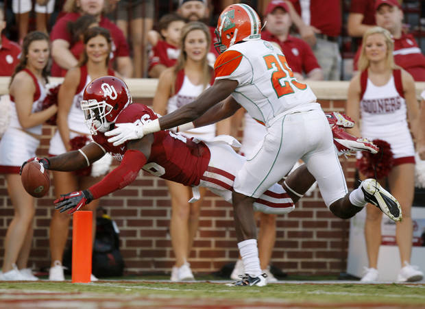 Oklahoma's Damien Williams (26) leaps past Florida A&M Rattlers safety John Ojo (25) for a touchdown during the college football game between the University of Oklahoma Sooners (OU) and Florida A&M Rattlers at Gaylord Family-Oklahoma Memorial Stadium in Norman, Okla., Saturday, Sept. 8, 2012. Photo by Bryan Terry, The Oklahoman