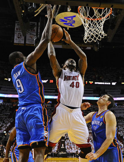 Miami Heat power forward Udonis Haslem (40) shoots between Oklahoma City Thunder power forward Serge Ibaka (9) from Republic of Congo and power forward Nick Collison (4) during the first half at Game 3 of the NBA Finals basketball series, Sunday, June 17, 2012, in Miami. (AP Photo/Larry W. Smith, Pool) ORG XMIT: NBA133