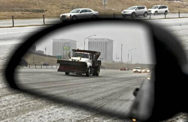 A sand truck reflects in a mirror as it covers the Lake Hefner Parkway as morning traffic navigates its way on icy roads on Thursday Dec. 24, 2009, in  Oklahoma City, Okla. Photo by Chris Landsberger