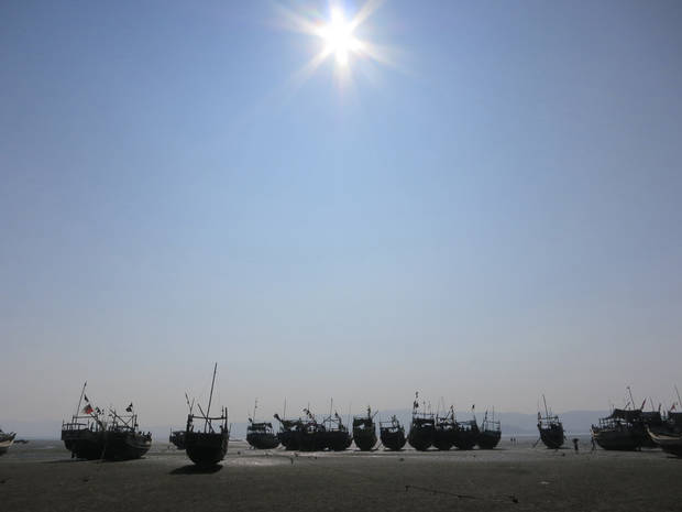 In this Sunday, Nov. 11, 2012 photo, a flotilla of wooden fishing boats belonging to Muslim refugees who fled the Myanmar port of Kyaukphu sit anchored during low tide on a beach in Sin Thet Maw, Myanmar. Stranded beside their decrepit flotilla of wooden boats, on a muddy beach far from home, the Muslim refugees tell story after terrifying story of their exodus from a once-peaceful town on Myanmar's western coast. (AP Photo/Todd Pitman)