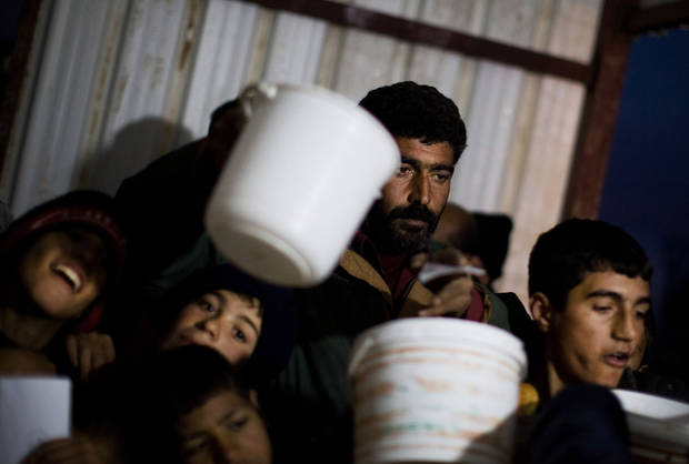 Syrians wait in line for food distribution at a refugee camp near the Turkish border, in Azaz, Syria, Sunday, Dec. 9, 2012. (AP Photo/Manu Brabo)