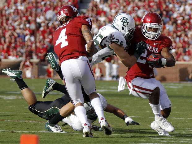 Oklahoma's Brennan Clay (24) is hit by Baylor's Terrence Singleton (24) as Kenny Stills (4) provides a block during the college football game between the University of Oklahoma Sooners (OU) and Baylor University Bears (BU) at Gaylord Family - Oklahoma Memorial Stadium on Saturday, Nov. 10, 2012, in Norman, Okla.  Photo by Chris Landsberger, The Oklahoman