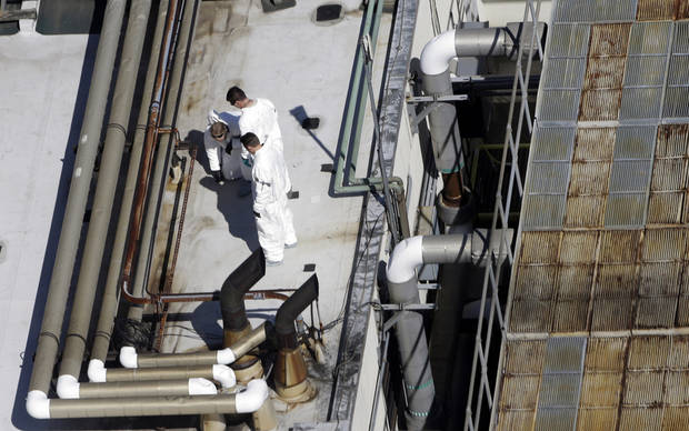Investigators inspect the roof of a building across the street from the area where a bomb exploded near the Boston Marathon finish line, Thursday, April 18, 2013, in Boston. Investigators in white jumpsuits fanned out across the streets, rooftops and awnings around the blast site in search of clues.  (AP Photo/Julio Cortez)