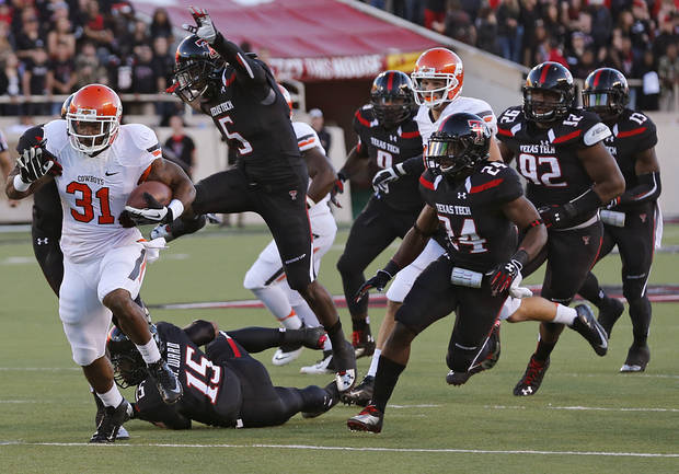 Oklahoma State 's Jeremy Smith (31) runs past the Texas Tech defense during the college football game between the Oklahoma State University Cowboys (OSU) and the Texas Tech University Red Raiders (TTU) at Jones AT&T Stadium in Lubbock, Tex. on Saturday, Nov. 2, 2013.  Photo by Chris Landsberger, The Oklahoman