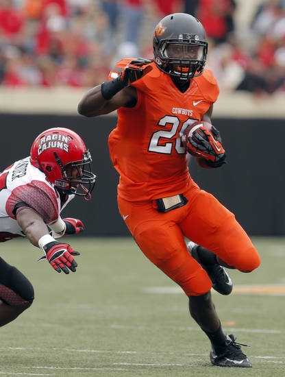 Oklahoma State's Desmond Roland (26) rushes as Louisiana-Lafayette's Tyren Alexander (29) tries to tackle him during a college football game between Oklahoma State University (OSU) and the University of Louisiana-Lafayette (ULL) at Boone Pickens Stadium in Stillwater, Okla., Saturday, Sept. 15, 2012. Photo by Sarah Phipps, The Oklahoman