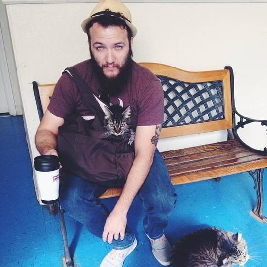 """David Bizzaro sits on a bench at the vet's office with his cat, Toby. Bizarro filmed """"The Girl From Normandy,""""which will be shown at Oklahoma City's Internet Cat Video Festival on Saturday. The video features a different cat, Rita. Photo provided"""