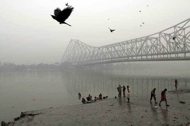 Indians bathe on the banks of the River Ganges River beside the landmark, Howrah Bridge on a cold winter morning in Kolkata, India, Friday, Jan. 11, 2013. More than 100 people have died of exposure as several parts of India deal with historically cold temperatures. (AP Photo/Bikas Das)