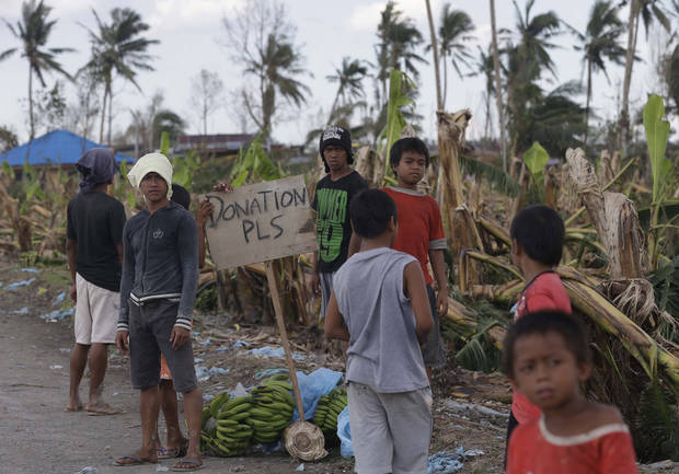 Residents affected by typhoon Bopha beg for aid from passing motorists along a highway at Montevista township, Compostela Valley in southern Philippines Sunday Dec. 9, 2012. The number of missing in the wake of a typhoon that devastated parts of the southern Philippines has jumped to nearly 900 after families and fishing companies reported losing contact with more than 300 fishermen in the South China Sea and Pacific Ocean, officials said Sunday. (AP Photo/Bullit Marquez)