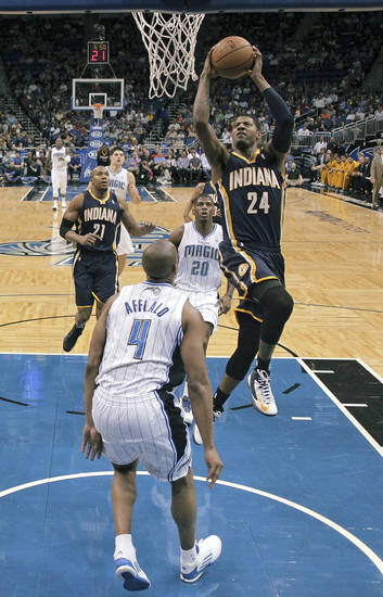 Indiana Pacers' Paul George (24) shoots between Orlando Magic's DeQuan Jones (20) and Arron Afflalo (4) during the first half of an NBA basketball game, Wednesday, Jan. 16, 2013, in Orlando, Fla. (AP Photo/John Raoux)