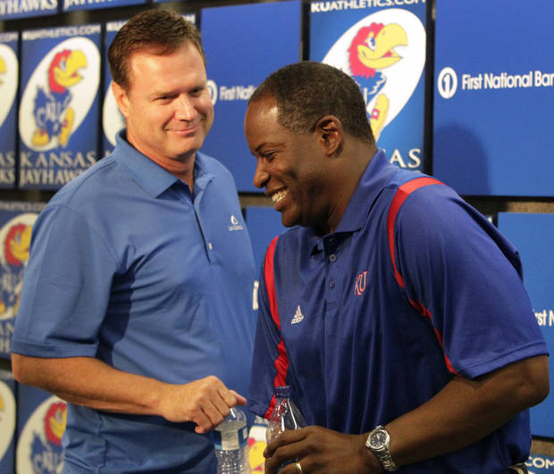 Kansas basketball coach Bill Self, left, and football coach Turner Gill smile as they leave a news conference in Allen Fieldhouse Tuesday, June 15, 2010, in Lawrence, Kan. (AP Photo/Orlin Wagner) ORG XMIT: KSOW101