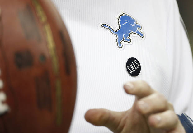 A Sandy Hook Elementary School pin is worn by a Detroit Lions assistant coach before the Lions' NFL football game against the Atlanta Falcons at Ford Field in Detroit, Saturday, Dec. 22, 2012. (AP Photo/Carlos Osorio)