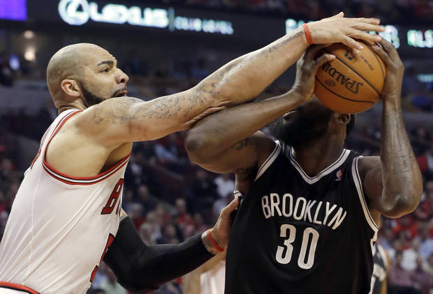 Chicago Bulls forward Carlos Boozer, left, defends against Brooklyn Nets forward Reggie Evans during the first half in Game 6 of their first-round NBA basketball playoff series in Chicago, Thursday, May 2, 2013. (AP Photo/Nam Y. Huh)