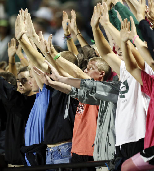 Edmond Santa Fe fans raise their hands during a high school football game between Mustang and Edmond Santa Fe in Mustang, Okla., Friday, Sept. 28, 2012. Photo by Nate Billings, The Oklahoman