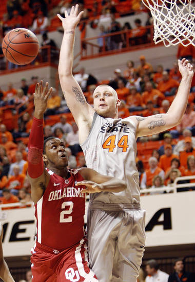 OU's Steven Pledger (2) tries to get a shot past Philip Jurick (44) of OSU in the first half during the Bedlam men's college basketball game between the Oklahoma State University Cowboys and the University of Oklahoma Sooners at Gallagher-Iba Arena in Stillwater, Okla., Monday, Jan. 9, 2012. Photo by Nate Billings, The Oklahoman