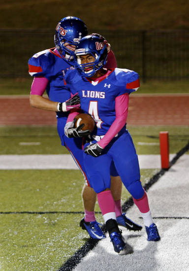 Jordan Norris (4) is congratulated after a touchdown by Corban Lawrence as the Moore Lions play the Lawton Eisenhower Eagles in a high school football game on Friday, Oct. 5, 2012, in Moore, Okla.  Photo by Steve Sisney, The Oklahoman